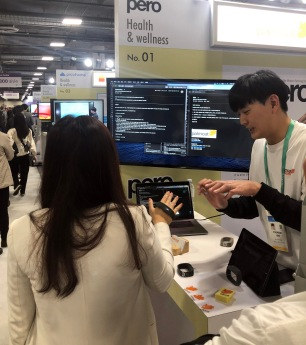 Exhibitor demonstrating a wearable computer mouse, shaped like a small rubber band bracelet.