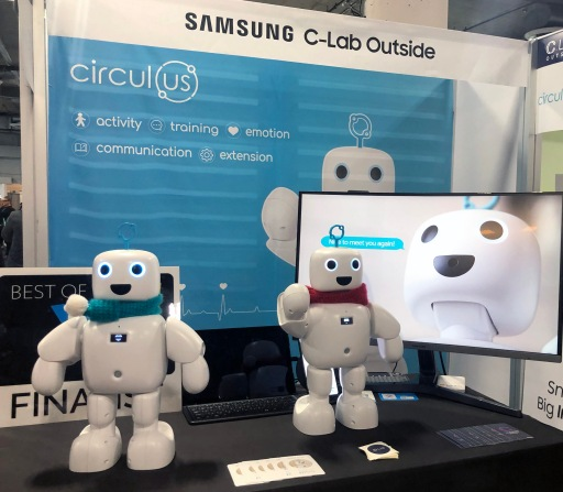 2 white plastic robots, about 1 foot tall, in front of sign that says: Samsung C-Lab Outside circulus activity, training, emotion, communication, extension.
