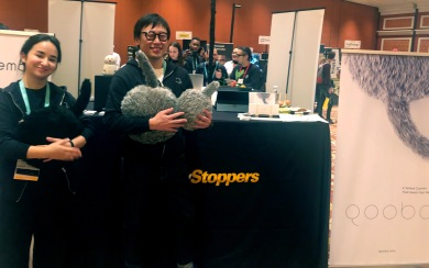 2 exhibitors holding Qooboo furry tail-wagging pillows.