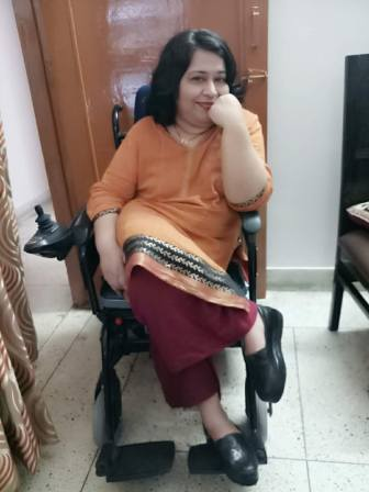 Abha Khetarpal, an Indian woman, sitting in her power chair and smiling. She is wearing a beautiful orange tunic and deep red pants.