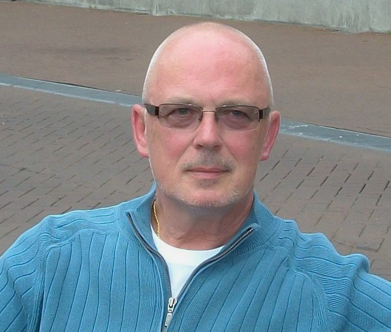 Photo of author Bob Goldstraw, a white adult man. He is wear slightly tinted glasses and a blue sweater.