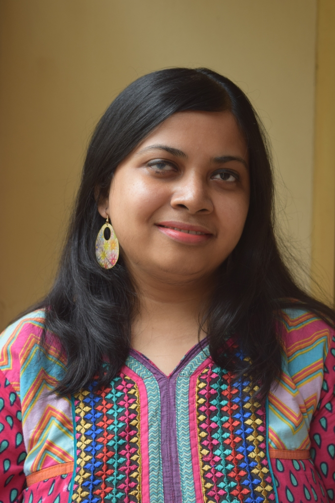 Author photo of Arundhati Nath, an Indian woman with shoulder length black hair. She is wearing a bright patterned shirt.