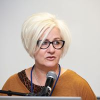 Author photo of Shelley Tremain, a white woman with jaw length white-blonde hair. She is speaking into a microphone.